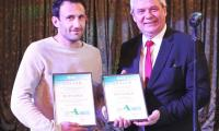 """Представител на българска фирма се радва на двете награди от Конкурса за иновации на """"Агра 2002"""", като  едната е за световна новост. Дипломите  връчи председателят на Селскостопанската академия проф. д-р инж. Мартин Банов  (вдясно)."""